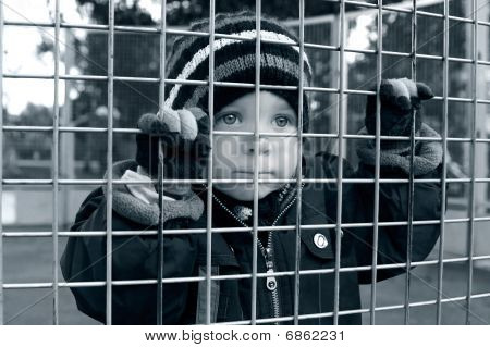 Serious Child Looking Through Fence
