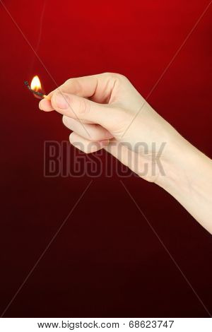 Burning match in female hand, on dark red background