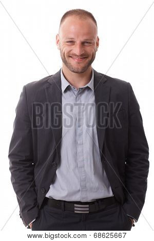 Portrait of happy smiling businessman standing with hands in pockets, looking at camera.