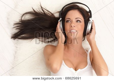 Sexy woman listening to music through headphones, lying on floor, smiling, looking away.