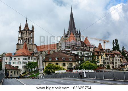 LAUSANNE, SWITZERLAND - JULY 7, 2014: The Cathedral of Notre Dame of Lausanne rises above the city. The Cathedral is currently undergoing renovation and is partially covered with scaffolding.