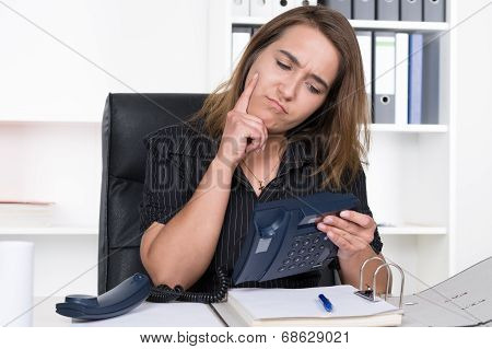 Young Woman Is Sceptically Looking At A Telephone