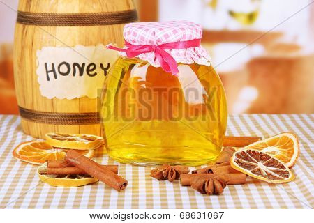Jar of honey, wooden barrel, drizzler and dried lemon slices on bright background