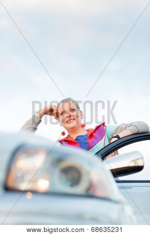 Portrait of a cheerful female teen driver, by her new car, looking very happy