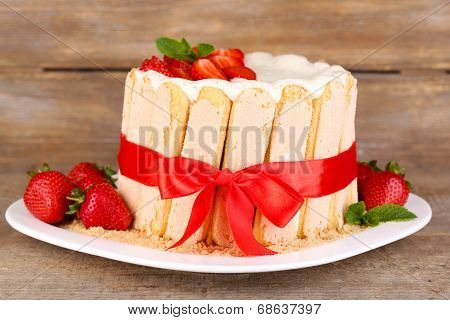 Tasty cake Charlotte with fresh strawberries on wooden table