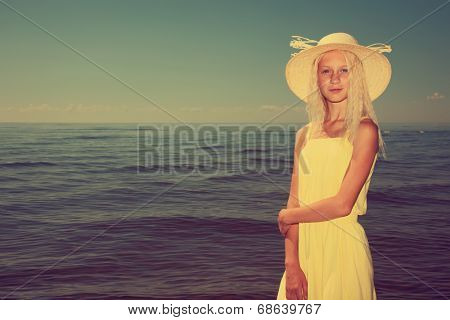 Beautiful teenage girl wearing yellow dress and hat next to the sea.
