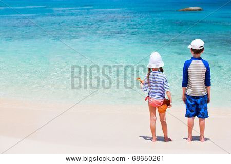 Little kids in rash guards for sun protection on tropical beach during summer vacation