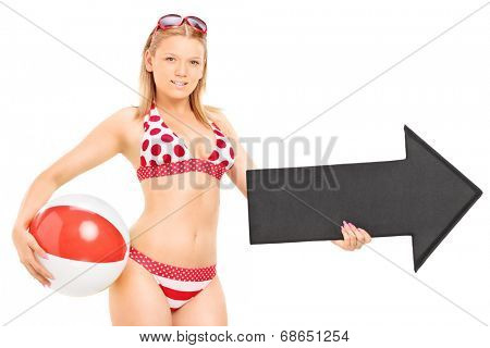 Woman in bikini holding a beach ball and an arrow pointing right isolated on white background
