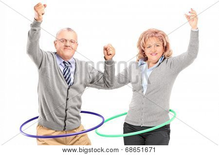 Mature man and woman exercising with hula hoop isolated against white background