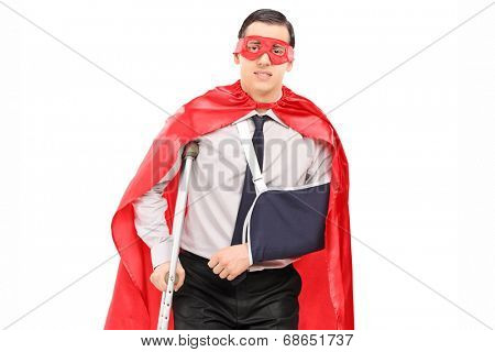 Male superhero with broken arm and a leg isolated against white background