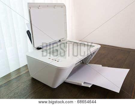 Printer with blank paper on a wood table
