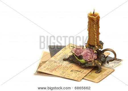 Antique Bronze Candlestick, Burning Candle, Roses And Old Photos