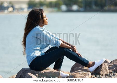 thoughtful african woman sitting by the harbour