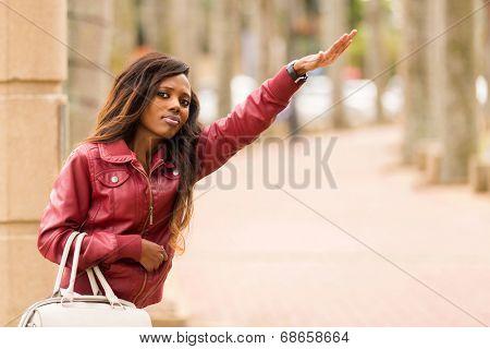 pretty african woman hailing a taxi cab