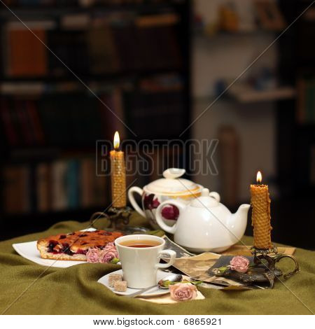 Cup Of Tea Against A Background Of Candles, Cake, Flowers And Old Photographs