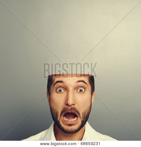 scared screaming man with open head over grey background