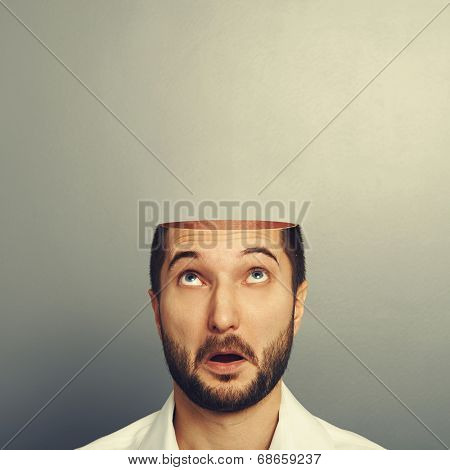 surprised man looking up at his open empty head. photo over grey background