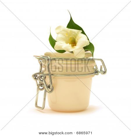 Jar With Some White Creamy Substance, White Flower And Green Leaves