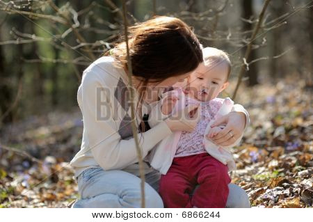 Little Girl And Her Mother In A Forest