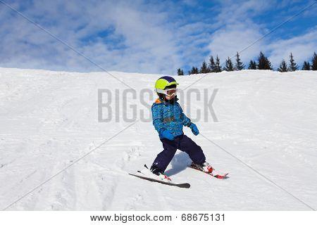 Boy in ski mask skiing on snow downhill