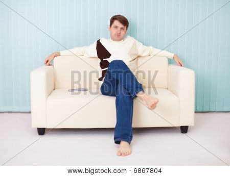 Young Man Sits Comfortably On Soft Sofa