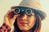 foto of binoculars  - Young traveler woman in hat looks through binoculars - JPG