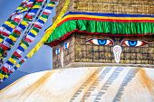 picture of all seeing eye  - Buddha eyes close up with prayer flags at Bodhnath stupa in Kathmandu valley Nepal - JPG