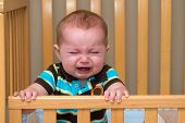foto of cry  - Crying unhappy baby standing in his crib - JPG