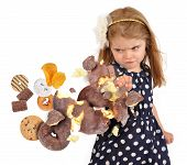 pic of child obesity  - A little child is punching a chocolate donut as cookies and junk food are coming to her for a health or hunger concept on a white background - JPG
