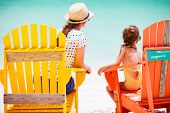 image of daughter  - Back view of mother and daughter family sitting on colorful wooden chairs at tropical beach enjoying summer vacation - JPG