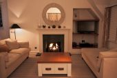 stock photo of cozy hearth  - A luxurious modern living room with comfortable couches and a lit fire - JPG