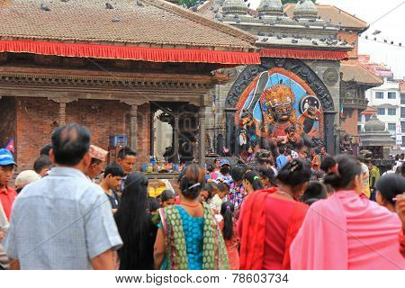 KATHMANDU, NEPAL - APRIL 2014 : Devotees worshipping Kal Bhairav at Kathmandu Durbar Square in Kathmandu, Nepal on 12 April 2014. Bhairav represents deity Shiva in his destructive manifestation.