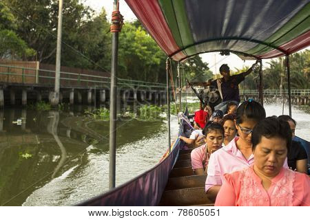 BANGKOK, THAILAND - DEC 19, 2014: A long-tail boat carrying local people passing on the Chao Praya River. Long-tail boats are a cheap (15 baht/ $0,5) form of river transport in the Thai capital.