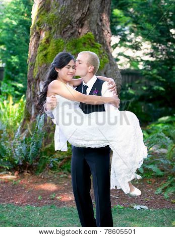 Caucasian Groom Carrying His Biracial Bride Outdoors, With A Kiss