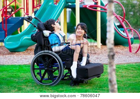 Sister Sitting Next To Disabled Brother In Wheelchair At Playground