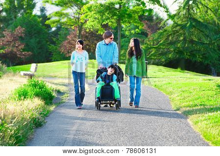 Disabled Boy In Wheelchair Walking With Family Outdoors On Sunny Day In Park