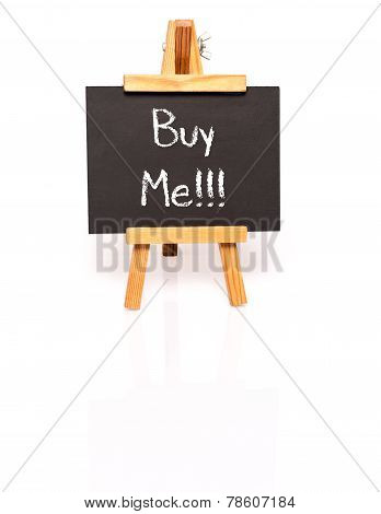 Buy Me. Blackboard with text and easel.