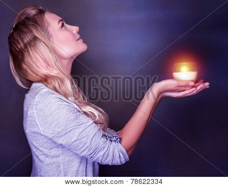 Side view of beautiful woman with candle in hands looking up on dark background, praying about her dreams and wishes, Christmas holiday concept