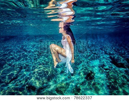 Beautiful dance underwater, gorgeous sportive woman wearing long white dress, dive to clear blue sea, zen balance and meditation concept