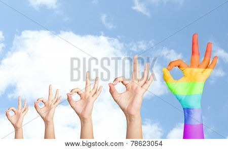 Man's hands on sky background, one hand painted as rainbow flag