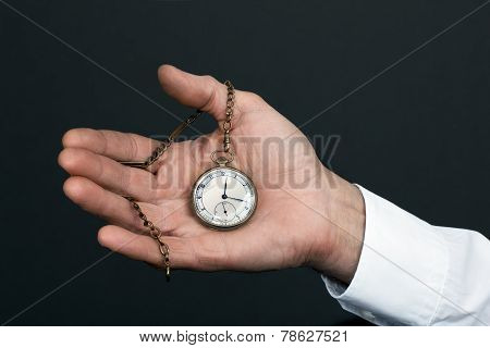 Old Man's Hand With A Vintage Clock