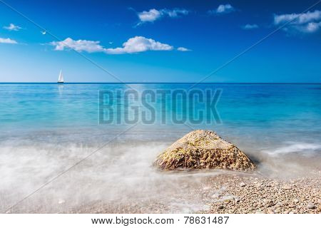 Stone Washed By The Waves And The Boat Sails