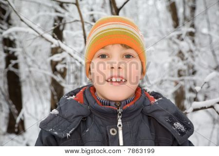 Smiling Boy In Cap In Wood In Winter