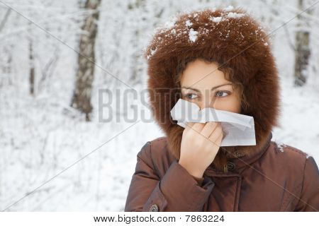 Young Woman With Scarf Blowing Nose In Wood In Winter