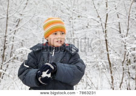 Boy Keeps In Hands Snowball In Wood In Winter, Looking Aside