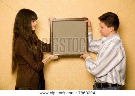 Beautiful Woman And Smiling Man With Picture In Frame In Hands
