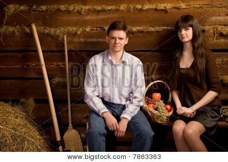 Young Man And Woman Near Basket Of Fruit Sitting On Bench
