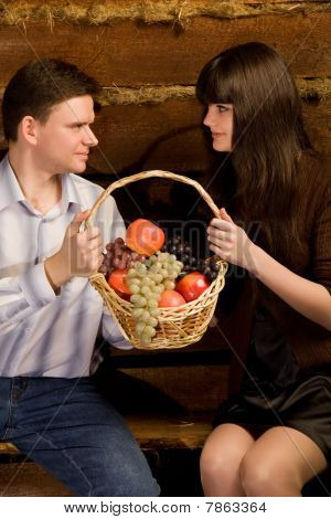 Man And Young Woman With Basket Of Fruit Sitting On Bench