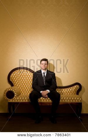 Businessman In Suit Sitting On Sofa In Room