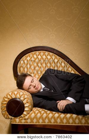 Businessman In Suit Sleeping On Sofa In Room